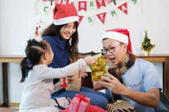 Merry Christmas and Happy New Year holidays. Family opening gift Stock Photography