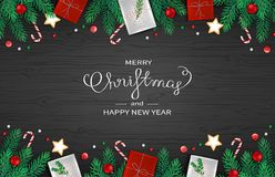 Merry Christmas and Happy New Year horizontal Web Banner Template. Festive Decoration with fir branches, gifts, candy cane. Lollipops, balls on black wooden Royalty Free Stock Image