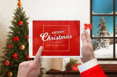 Merry Christmas and Happy New Year massage on white tablet in Santa Claus hands. Christmas tree and decorations in background Royalty Free Stock Photography