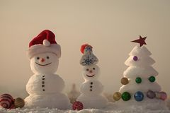 Merry Christmas and happy new year. Holidays celebration concept. xmas tree decorated with star and balls. Snow sculptures on rosy sky background. Snowmen with royalty free stock photography