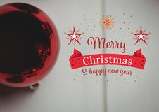 Merry christmas and happy new year message against red christmas bauble Royalty Free Stock Photo