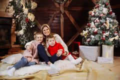 Merry Christmas and Happy New Year. Momand children having fun near Christmas tree indoors near Christmas tree. stock photo