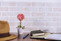 Merry Christmas and Happy New Year picture. Seasonal and holiday scenery brick wall, flower, book, a cup of coffee Stock Image