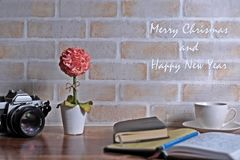 Merry Christmas and Happy New Year picture. Seasonal and holiday scenery brick wall, flower, book, a cup of coffee and old camera Stock Photography