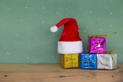 Red Santa hat with colorful gift box on wooden floorand. Merry christmas Happy new year. Red Santa hat with colorful gift box on wooden floorand and scene green Royalty Free Stock Image