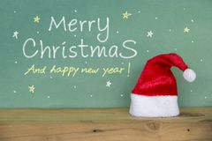 Merry christmas Happy new year. Red Santa hat. On wooden floorand and scene green board background space leave blank for writing greetings and Have Snow Stars Royalty Free Stock Images