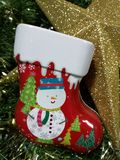 Merry Christmas and Happy New Year, snowman sock Tin Box and gold star with green tinsel. Background Royalty Free Stock Photos