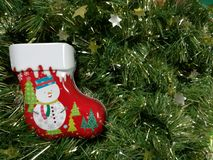 Merry Christmas and Happy New Year, snowman sock Tin Box with green tinsel. Background Royalty Free Stock Images