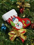 Merry Christmas and Happy New Year, snowman sock Tin Box, ribbon and ornaments decoration with green tinsel background. On vertical Stock Photo
