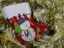 Merry Christmas and Happy New Year, snowman sock Tin Box with white and gold tinsel. Background Stock Photography