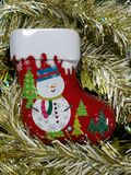 Merry Christmas and Happy New Year, snowman sock Tin Box with white and gold tinsel background. On vertical Royalty Free Stock Photos