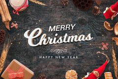 Merry Christmas and happy New Year text on black wooden desk with Christmas decorations. Top view Royalty Free Stock Image
