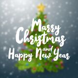 Merry Christmas and happy New Year text on blurred background with decorated christmas tree. Stock Image
