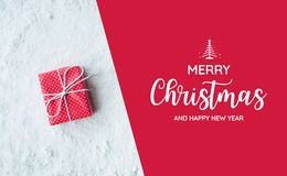 Merry christmas and happy new year text with gift box,present. On snow background.For festival and celebration concepts ideas.Top view Stock Image