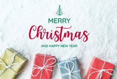 Merry christmas and happy new year text with gift box,present. On snow background.For festival and celebration concepts ideas.Top view Stock Photos
