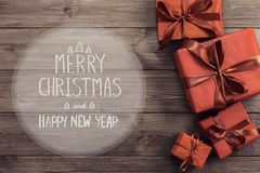 Merry Christmas and Happy New Year text with gift boxes. On wooden background, top view royalty free stock photo