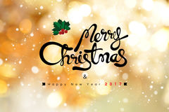 Merry Christmas and Happy New Year 2017 text on shiny gold bokeh. Background with snowfall