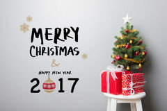 MERRY CHRISTMAS and HAPPY NEW YEAR 2017 text on the wall. Gift boxes and small decorated Christmas tree on the chair with MERRY CHRISTMAS and HAPPY NEW YEAR 2017