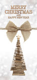 Merry christmas and happy new year text with wooden tree and jut. E ribbon bow Royalty Free Stock Photography