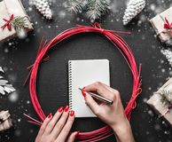 Merry Christmas and happy New Year. Top view of female hands writing a xmas letter. Christmas presents and decorations placed on black table next to the letter Royalty Free Stock Image