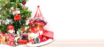 Merry Christmas and Happy New Year. Winter season. Santa and gift on tree with snow on wood. Isolated on white background Stock Photo