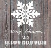 Merry Christmas and Happy New Year on wooden board with snowflake. Close Royalty Free Stock Photography