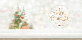 Merry christmas and happy new year wreath at White wood table top at blur bokeh christmas tree decor with string light background. When show falling,Winter royalty free stock images