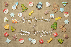 Merry Christmas and Happy New Year! written among gingerbread cookies. Stock Photos