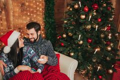 Merry Christmas and Happy New Year . Young couple celebrating holiday at home. The man is holding the remote from the TV royalty free stock image