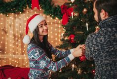 Merry Christmas and Happy New Year . Young couple celebrating holiday at home. Young woman and woman decorate the New Royalty Free Stock Images