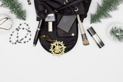 Merry Christmas and Happy newyear beauty and fashion concept. Flat lay of Christmas ornaments and black woman bag open out with royalty free stock photos