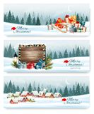 Merry Christmas Holiday Banners  with a winter village. And presents. Vector Stock Photos
