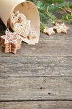 Merry christmas holiday decoration background. Traditional homemade Christmas gingerbread sugar frosting in paper envelope on wood royalty free stock photography