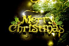 Merry Christmas inscription, fir and lights on chalk blackboard. Merry Christmas gold inscription, fir branhes and newyear lights on black background. Copy space stock image