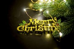 Merry Christmas inscription, fir and lights on chalk blackboard. Merry Christmas gold inscription, fir branhes and newyear lights on black background. Copy space royalty free stock images