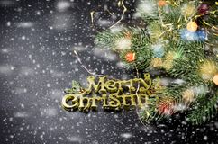 Merry Christmas inscription, fir and lights on chalk blackboard. Merry Christmas gold inscription, fir branhes and newyear lights on black background. Copy space royalty free stock photos