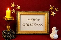 Merry Christmas, inscription, gold stars, angel, candle. Christmas is the Main Holiday of winter, the inscription in a gold vintage frame, vintage candle, gold royalty free stock images