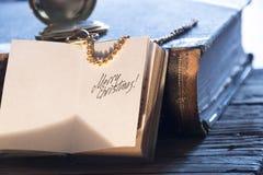 Merry christmas inscription, toned photo. Merry Christmas - inscription, gold pocket watch and old vintage book royalty free stock photo