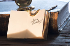 Merry christmas inscription, toned photo. Merry Christmas - inscription, gold pocket watch and old vintage book stock images