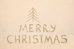 Merry Christmas inscription on wet yellow beach sand Royalty Free Stock Photo