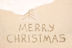 Merry Christmas inscription on wet yellow beach sand Stock Photos