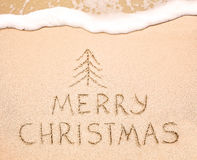 Merry Christmas inscription on wet yellow beach sand Stock Photo