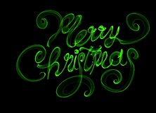 Merry Christmas isolated text written with flame fire light on black background. Green color.  Stock Images