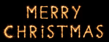 MERRY CHRISTMAS lettering drawn with bengali sparkles isolated on black. Background stock photos