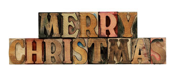 Merry Christmas in letterpress wood type. Merry Christmas in old, ink-stained letterpress wood type, all caps, isolated on white stock photography