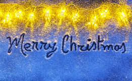 Merry Christmas letters handdrawn on snow surface with Garlands Stock Photo