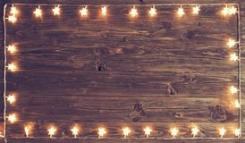 Merry Christmas! Christmas lights frame on wooden background with copy space.  royalty free stock photography