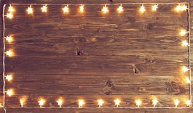 Merry Christmas! Christmas lights frame on wooden background with copy space.  stock photo
