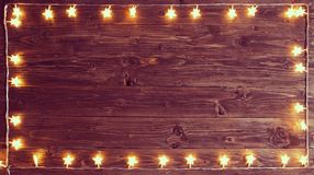 Merry Christmas! Christmas lights frame on wooden background with copy space.  stock photos