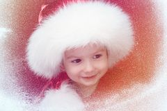 Merry Christmas little child on window looking at the winter. Kid and snowfall. Stock Images